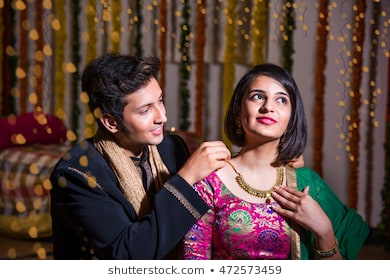 [Image: indian-husband-tying-presenting-necklace...573459.jpg]
