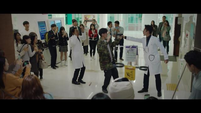 Kang Joon Sang menodongkan pistol miliknya, yang ternyata gas air mata, pada pasien pria.