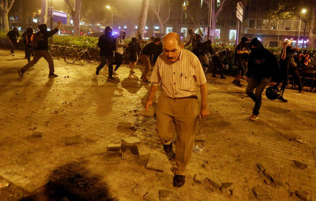 a-man-takes-away-rocks-from-the-protesters-during-catalonia-s-general-strike-in-barcelona-spain-octo