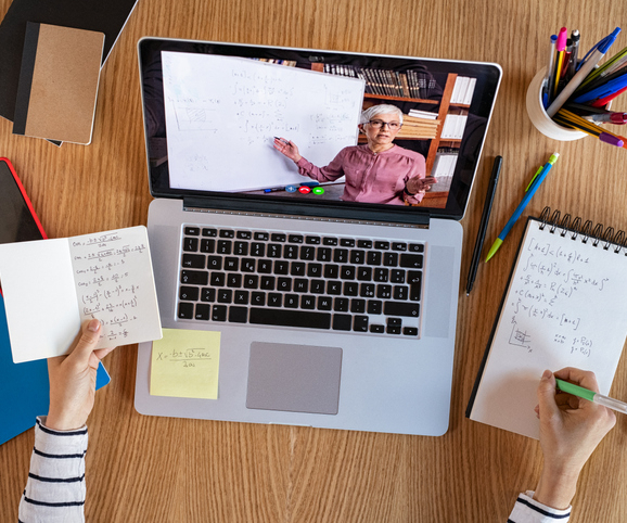 High-angle-view-of-video-conference-with-teacher-on-laptop-at-home-College-student-learning-maths-wh
