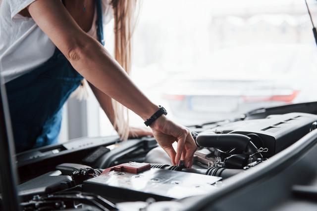On-the-lovely-job-Car-addicted-woman-repairs-black-car-indoors