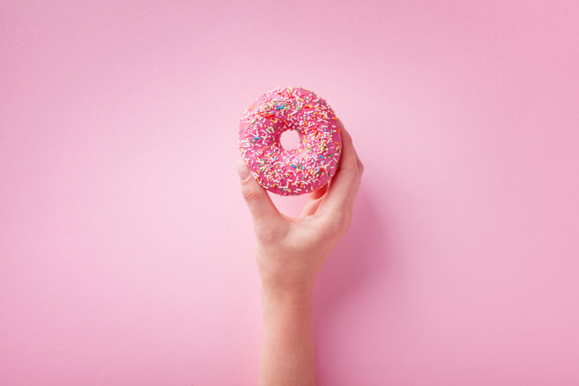 Woman-hand-holding-pink-donut-or-doughnut-on-pastel-background-Flat-lay
