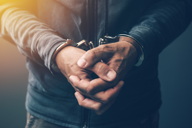 Arrested-computer-hacker-and-cyber-criminal-with-handcuffs-close-up-of-hands