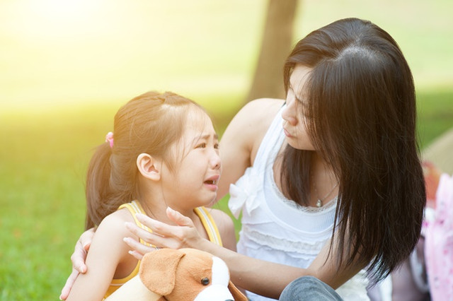Portrait-of-Asian-mother-comforting-her-crying-daughter-in-the-park-Family-outdoor-lifestyle