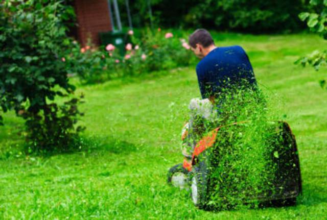 человек косит траву на газонокосилке