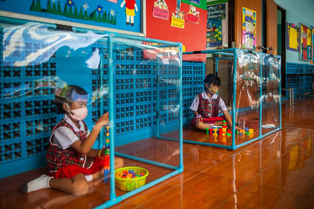 BANGKOK-THAILAND-AUGUST-10-Thai-kindergarteners-wear-face-masks-as-they-play-in-screened-in-play-are