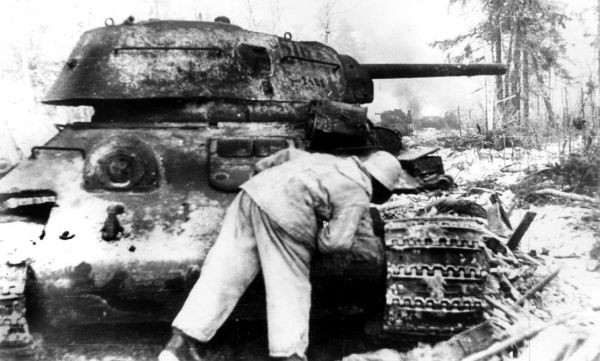 German soldier examines a wrecked T-34 tank