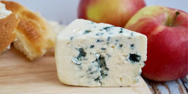 Сыр Тиролез, доска для резки еды и яблоки