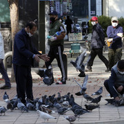 People-wearing-face-masks-to-help-protect-against-the-spread-of-the-coronavirus-feed-pigeons-on-a-st
