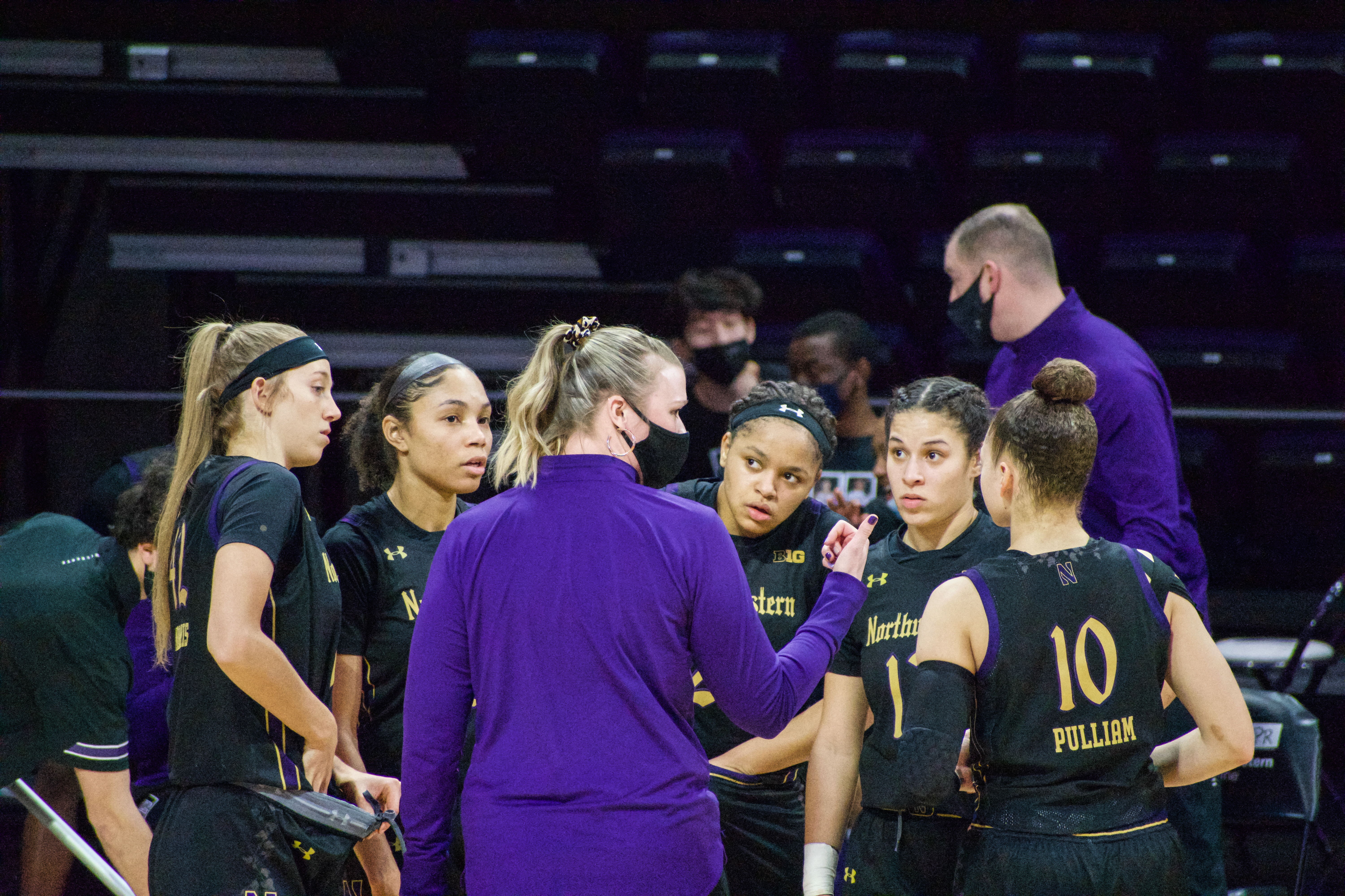 Five members of the women's basketball team, wearing black, huddle around Popovec, wearing purple with her back to the camera.