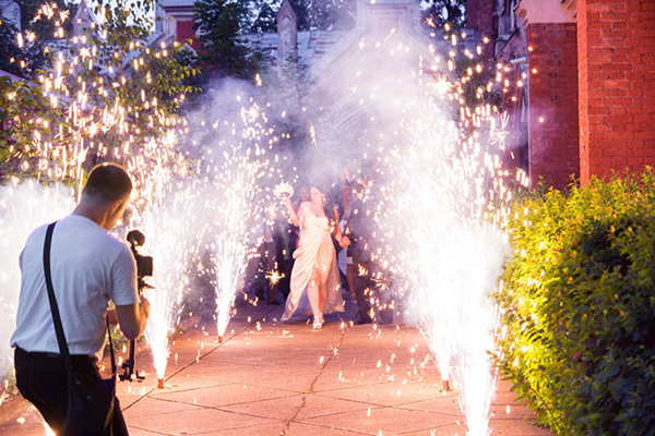 Photographer shooting bride and groom walking through sparklers