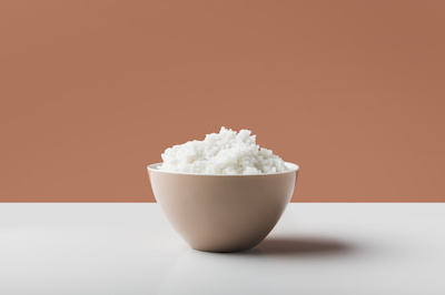 cooked-white-boiled-rice-bowl-white-table-against-brown-background-23-2147901649