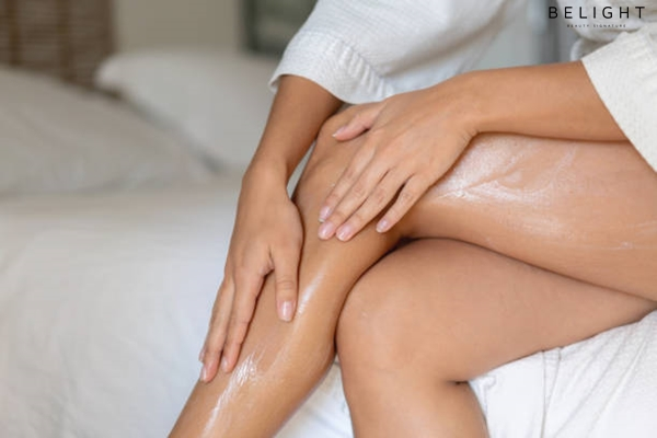 Close-up-on-a-woman-applying-moisturizing-cream-on-her-legs-skin-care-concepts