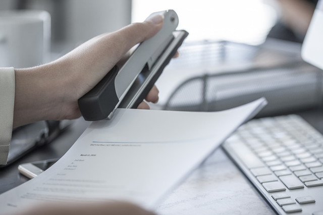 Close-up-of-woman-at-desk-stapling-a-document