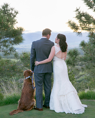 Couple embrace with dog standing next to them