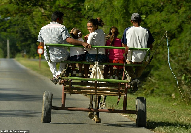 22160040-7785767-Cubans-ride-a-horse-carriage-in-Granma-province-on-November-15-2-a-35-1576170216485.jpg